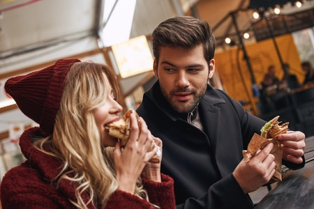 Young couple are eating out. Holding sandwiches at the street food market. Imagens