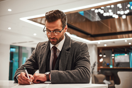 Man in Hotel check in at reception or front office, fulfills his profile Stock Photo