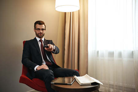 Businessman choosing chanel on TV on the red chair in hotel room Stock Photo
