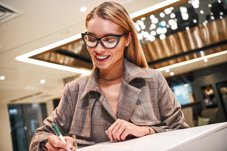 Businesswoman in hotel at reception or front office, fulfills her profile Stock Photo - 116354645