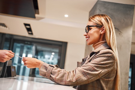 Young woman in hotel check in at reception or front office being given key card