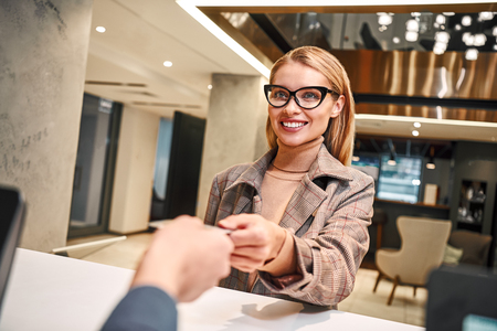 Young woman in hotel check in at reception or front office being given key card Stock Photo - 116354809