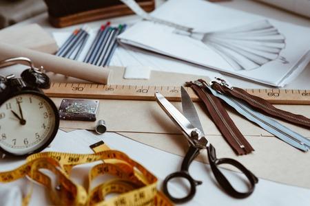 Attrezzi da sarto, forbici, metro a nastro e righello sul tavolo da lavoro sartoriale