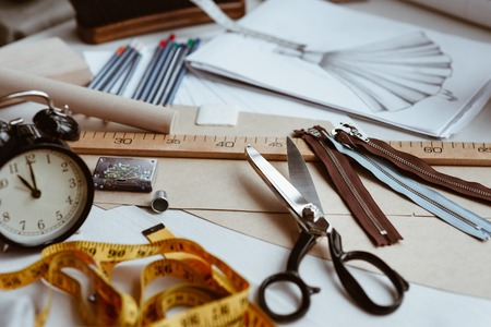 Tailors tools, scissors, measure tape and ruler on the sartorial work table
