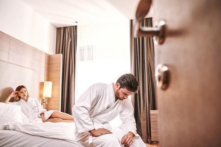 Hombre preocupado debilidad en la habitación del hotel. El hombre no puede hacer con su mujer