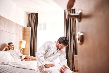 Weakness worried man in hotel room. Man cant make sex with his woman Stock fotó - 117063602