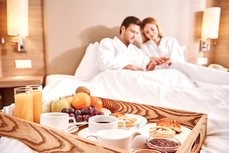 Food in a bed. Couple are hugging in hotel room bed 免版税图像