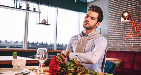 She should be soon. Man is worrying while waiting in restaurant Stock Photo