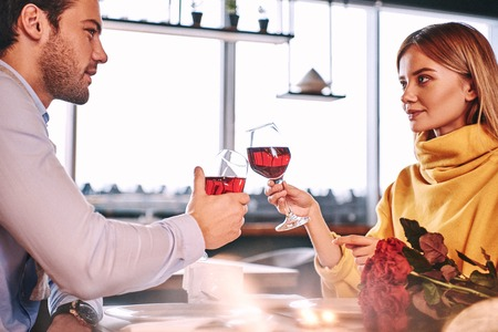 Solemn moments. Couple holding red wine in glasses in restaurant Banco de Imagens