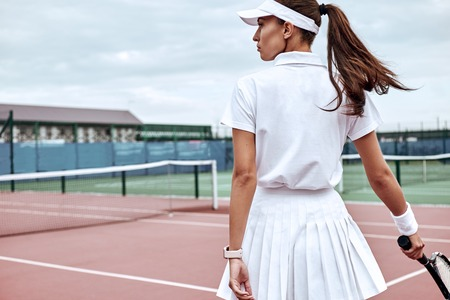 Nobody who ever gave his best regretted it. Beautiful girl is going to play tennis on the court Stock Photo