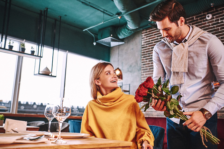 Red roses for woman. Man in blue shirt surprised his pretty blonde girlfriend 版權商用圖片