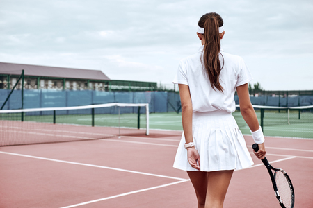 Always make a total effort, even when the odds are against you. Woman is going to play tennis on the court Фото со стока - 117064178