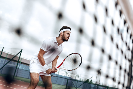 Stay focused. Handsome tennis player is standing on the court, ready for the shot Stock Photo