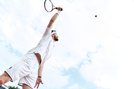 Stay focused. Tennis player is looking at the ball in the air