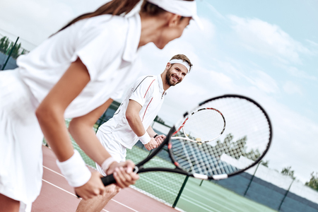 Active weekend together. Couple plays tennis Stok Fotoğraf - 117064200