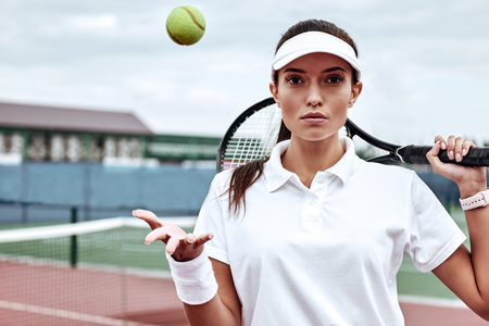 Champions keep playing until they get it right. Beautiful woman in white polo with the racket and the bal standing on the tennis court Reklamní fotografie