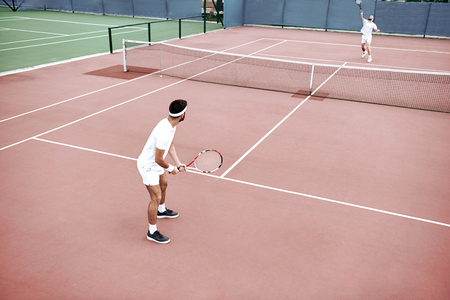 Success is one percent inspiration, ninety-nine percent perspiration. Two men are playing on the court Stock Photo