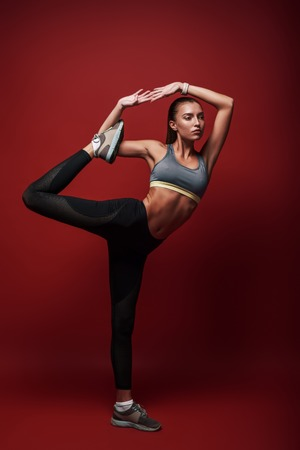 The best training program in the world is absolutely worthless without the will to execute it properly, consistently, and with intensity. Sportswoman standing over red background, stretching her body