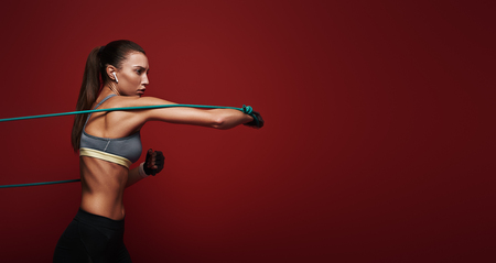 Everything is possible. Sportswoman performs exercises with resistance band over red background