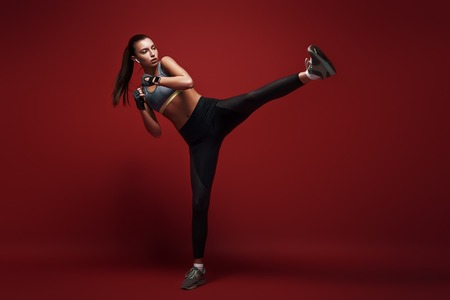 Born to win. Attractive sportswoman doing kickboxing exercises isolated over red background Stockfoto