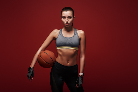 Are you ready to play? Sportswoman is training with ball standing over red background
