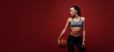 Do what you like. Sportswoman is training with ball standing over red background
