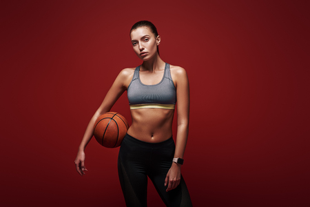 Winners train, losers complain. Sportswoman with ball standing over red background