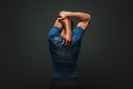 Even if you dont have time for a big workout, stretching in the morning and night really changes your body. Sportsman is stretching standing over dark background Reklamní fotografie
