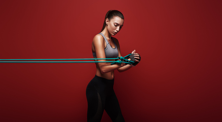 Never let good enough be enough! Sportswoman performs exercises with resistance band over red background