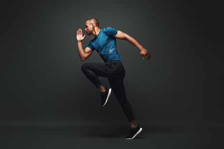 Deserve Victory. Sportsman jumping over dark background, he is ready to run Stock Photo