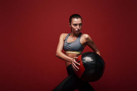 Your body hears everything your mind says. Sportswoman holds exercise ball standing over red background