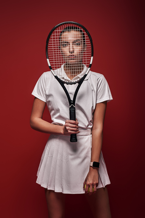 All it takes is all you've got! Young tennis player standing isolated over red background with a racket and a ball