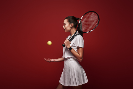 Talk with your raquet, play with your heart. Young tennis player standing isolated over red background with a racket and a ball
