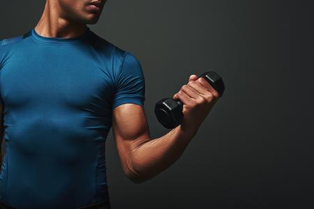 Stronger, Better, Faster. Dark skinned sportsman working out with dumbbells over dark background