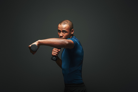 Everything is possible. Dark skinned sportsman working out with dumbbells over dark background
