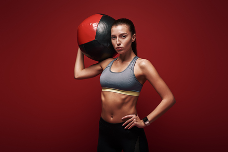 Create healthy habits, not restrictions. Sportswoman holds exercise ball standing over red background