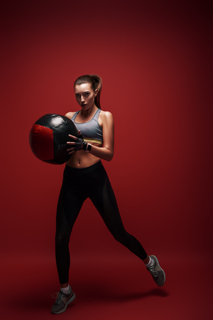 Power and beauty. Sportswoman jumping with a ball over red background Stock Photo