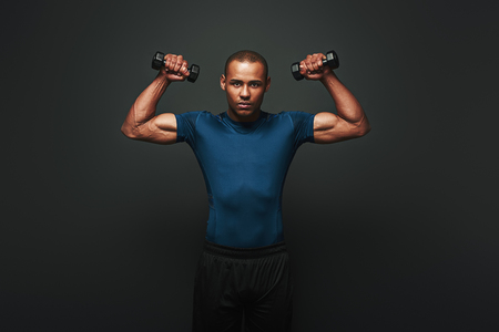 Stronger and faster. Dark skinned sportsman working out with dumbbells over dark background Stock Photo