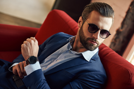 Looking just perfect...Young and sexy bearded businessman in sunglasses is looking away while sitting on office sofa Stock Photo