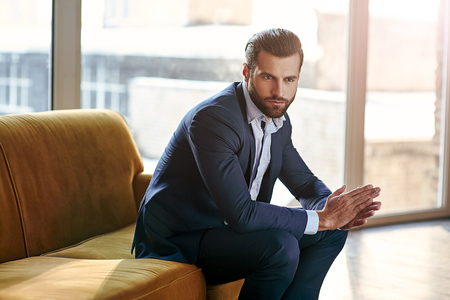Confident and concentrated. Thoughtful handsome businessman is thinking while sitting in his modern office about business concept while sitting on sofa Stock Photo