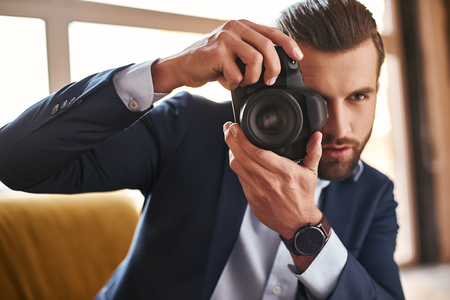 Young stylish businessman with camera in his hands taking pictures while sitting on sofa at modern office