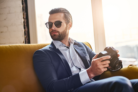 In search of inspiration. Successful young stylish businessman in sunglasses, is holding photo camera and thinking about something