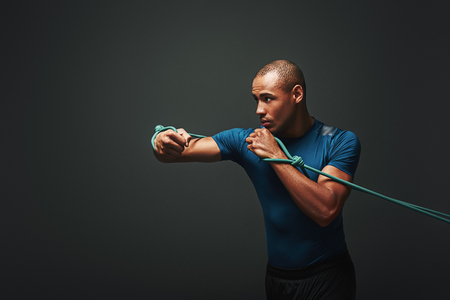 Sport is my lifestyle. Sportsman working out with resistance band over dark background 版權商用圖片