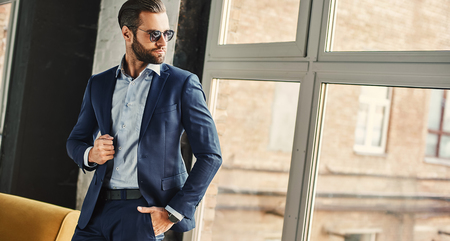 Confident and stylish. Businessman in sunglasses and fashion suit is thoughtfully looking in window while standing at office Stock Photo