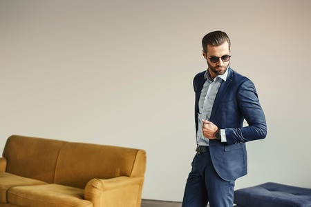 Portrait of stylish and attractive bearded businessman in sunglasses and classic suit.