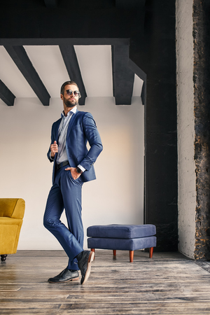 Successful businessman. Full height view of attractive bearded businessman in stylish suit at office