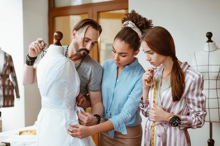 Designers masterpiese. Group of fashion designers measuring dress