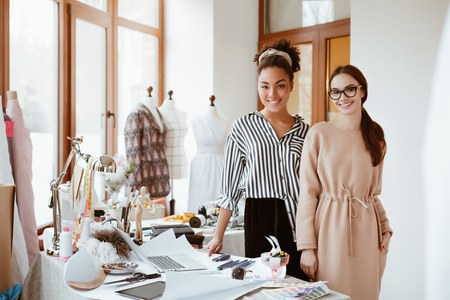 Two women stylists in design studio. Work process of modeling new clothes Stock Photo