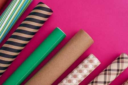 Pack your gifts with multicolored wrapping paper. Rolls of different wrapping paper. Stock Photo