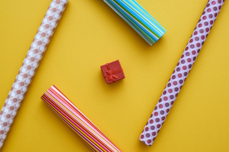 Easy Gift Packing. Set of colorful wrapping paper on yellow background. Stock Photo